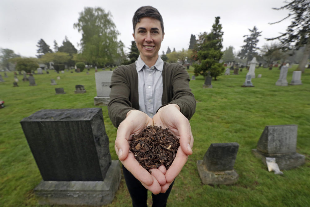 Katrina Spade, the founder and CEO of Recompose, displays a sample of the compost material left from the decomposition of a cow, using a combination of wood chips, alfalfa and straw, as she poses in a cemetery in Seattle. (Elaine Thompson/AP)