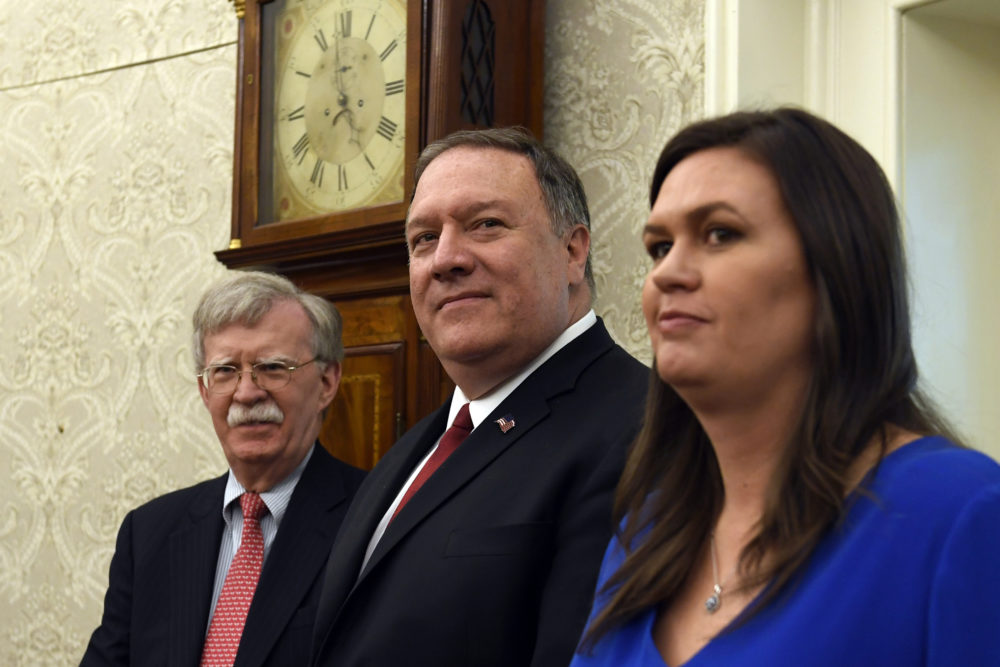 Secretary of State Mike Pompeo, center, flanked by national security adviser John Bolton, left, and White House press secretary Sarah Sanders, right, listen during the meeting between President Donald Trump and Japanese Prime Minister Shinzo Abe in the Oval Office of the White House in Washington, Friday, April 26, 2019. (Susan Walsh/AP)