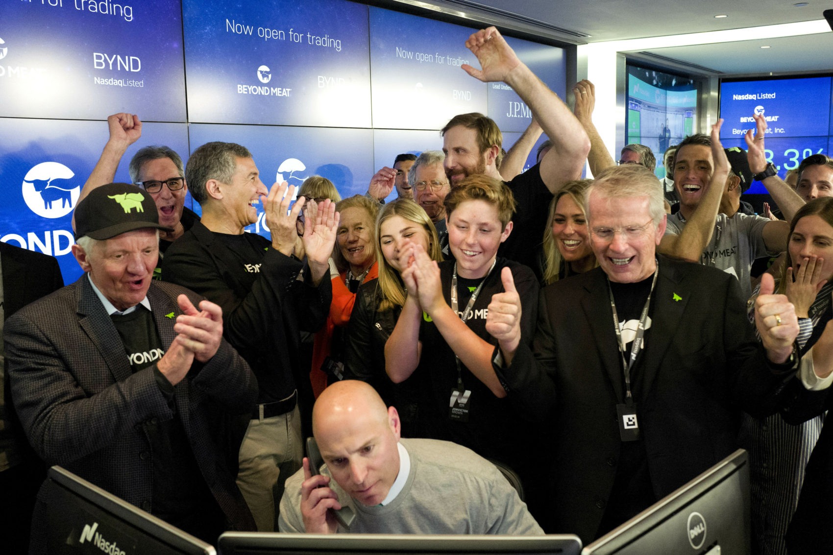 Ethan Brown, center background, CEO of Beyond Meat, raises his hand after his company's stock begins to trade, following its IPO at Nasdaq on May 2. California-based Beyond Meat makes burgers and sausages out of pea protein and other ingredients. (Mark Lennihan/AP).
