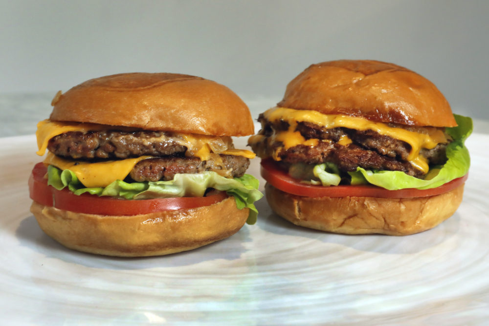 An Original Impossible Burger, left, and a Cali Burger, from Umami Burger, are shown in this photo in New York, Friday, May 3, 2019. (Richard Drew/AP)