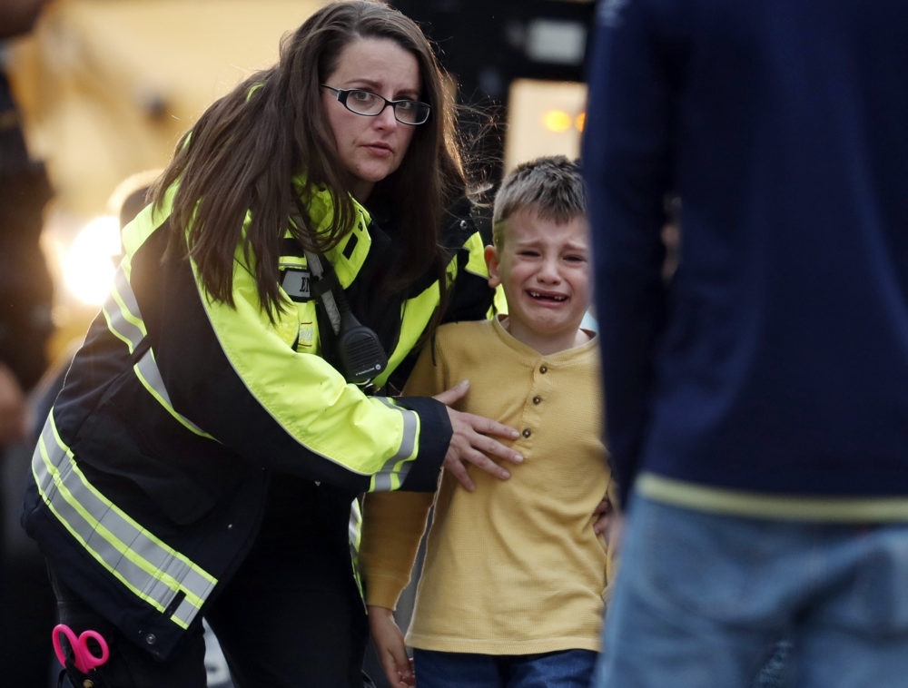 Officials guide students off a bus and into a recreation center where they were reunited with their parents after a shooting at a suburban Denver middle school Tuesday, May 7, 2019, in Highlands Ranch, Colo. (David Zalubowski/AP)
