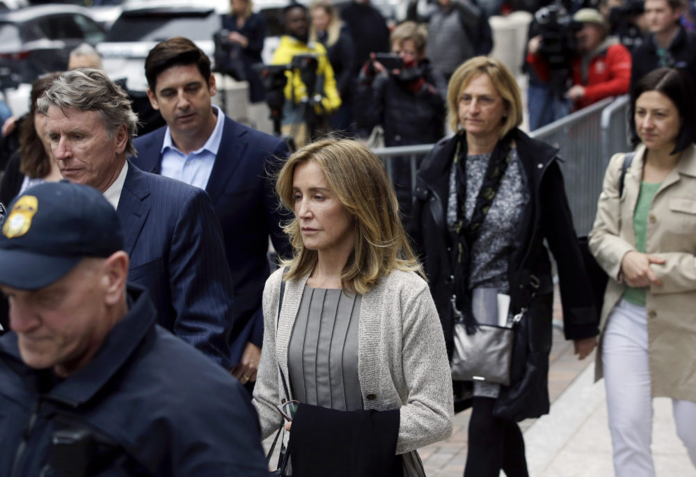 Felicity Huffman, center, departs Boston federal court with her brother, left, on Monday after she pleaded guilty to charges in a nationwide college admissions bribery scandal. (Steven Senne/AP)