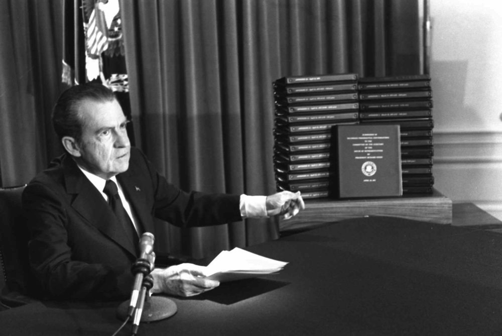 President Nixon gestures toward transcripts of White House tapes after announcing he would turn them over to House impeachment investigators and make them public in April 1974. (AP Photo)