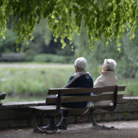 An elderly couple sits on a bench in a park in this 2014 file photo. (Martin Meissner/AP)