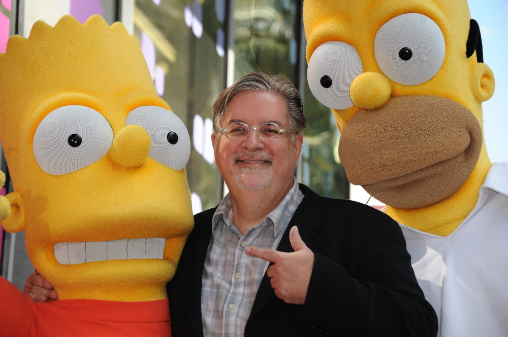 """Cartoonist Matt Groening, creator of """"The Simpsons,"""" poses with his characters Bart (left) and Homer Simpson. """"The Simpsons"""" celebrates its 30th anniversary this year. (Robyn Beck/AFP/Getty Images)"""