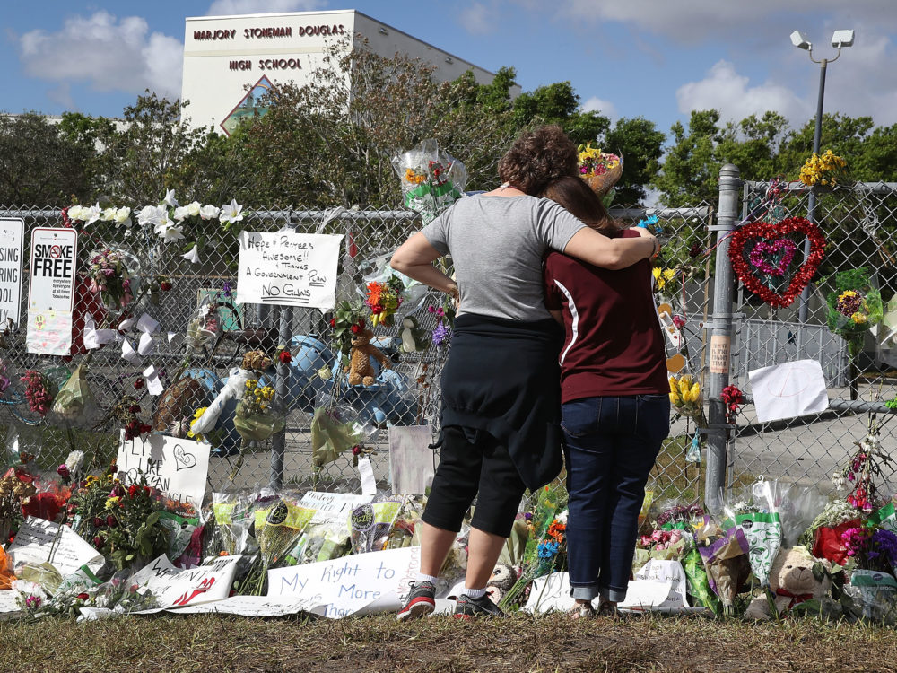 Two women look on at the memorial in front of Marjory Stoneman Douglas High School as teachers and staff are allowed to return to the school for the first time since the mass shooting on campus on Feb. 23, 2018 in Parkland, Fla. (Joe Raedle/Getty Images)
