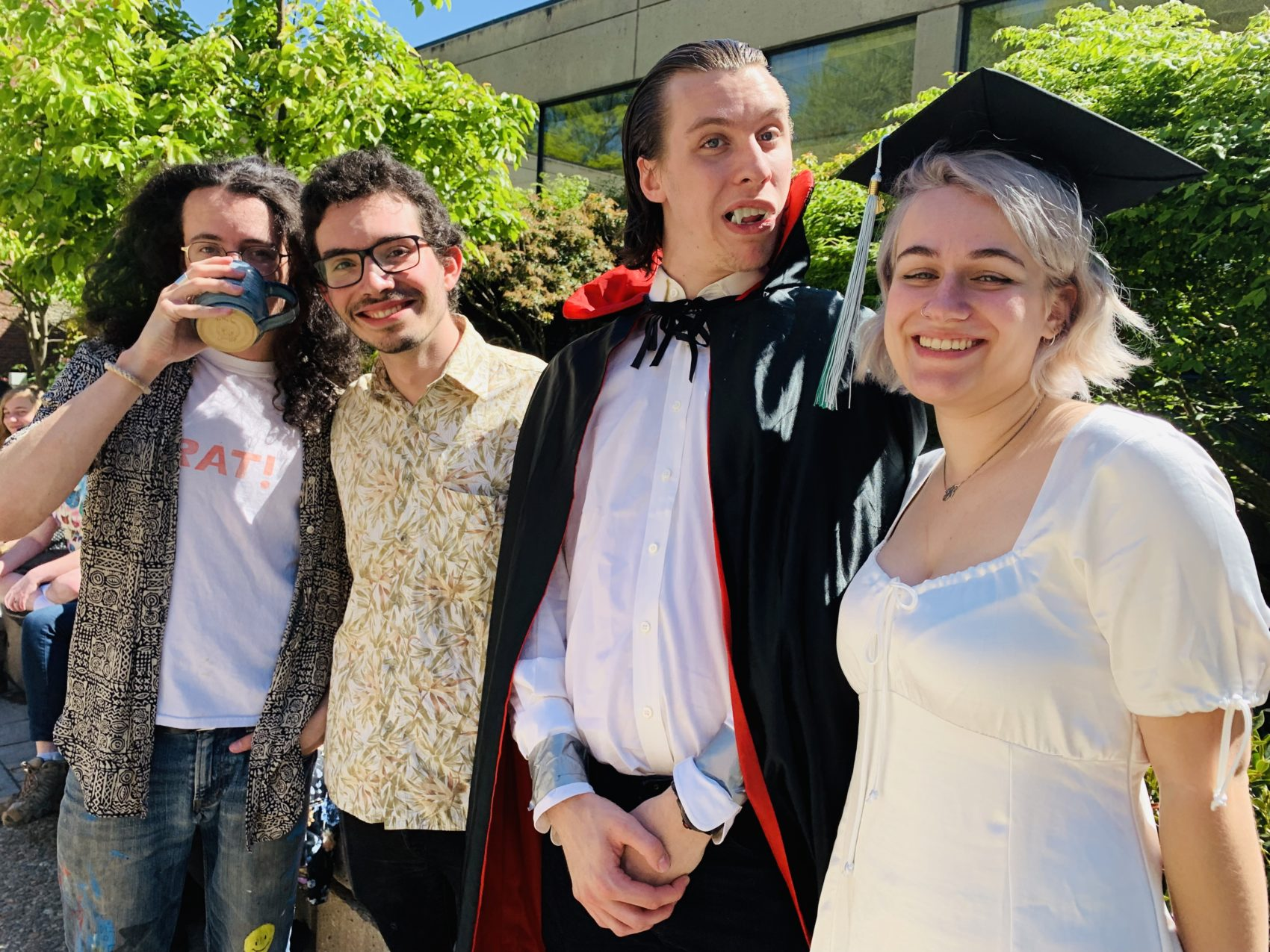 Friends Koby Leff, Walt Harms (dressed as Dracula) and Fiona Black wait with their fellow graduates before commencement kicks off. About half of the 295 students in line to graduate don't wear the traditional cap and gown. (Carrie Jung/WBUR)