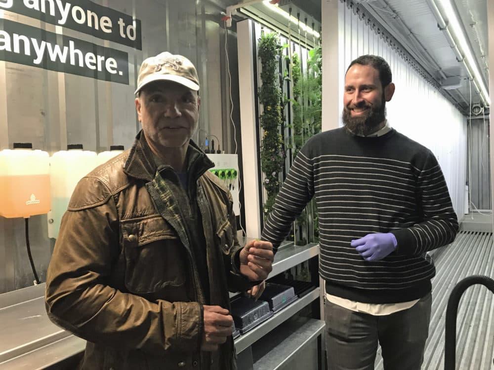 Spark Capital co-founder Todd Dagres, left, samples a piece of lettuce harvested by Freight Farms co-founder Brad McNamara. (Callum Borchers/WBUR)