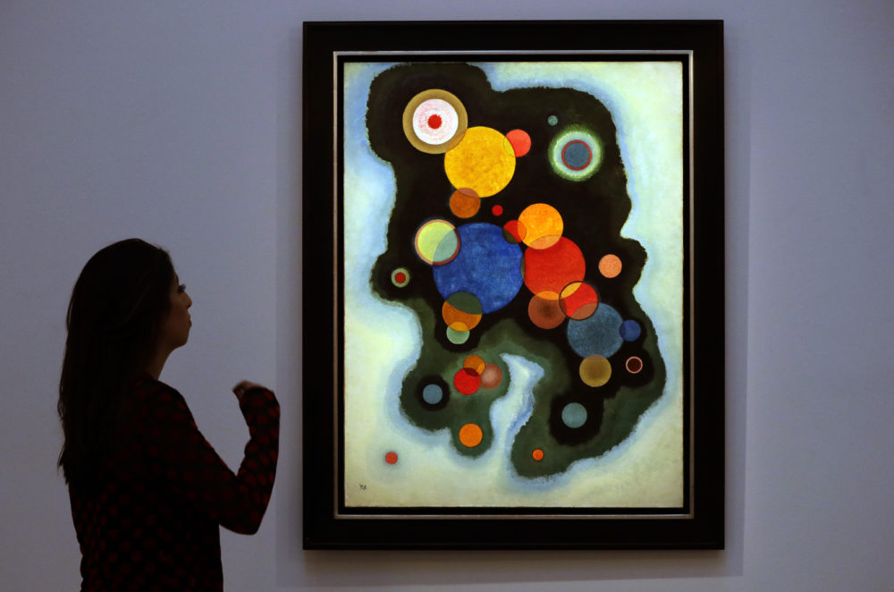 A Sotheby's employee looks at a painting by Wassily Kandinsky called 'Vertiefte Regung' (Deepened Impulse) at Sotheby's auction rooms in London, Feb. 20, 2019. (Kirsty Wigglesworth/AP)