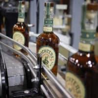Bottles of Michter's Kentucky Straight Bourbon move down a conveyor belt at Michter's Shively Distillery in Louisville, Ky. (Luke Sharrett for Here & Now)