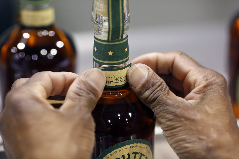 A distillery worker affixes a label to a bottle of Michter's Kentucky Straight Bourbon at the Michter's Shively Distillery in Louisville, Ky. (Luke Sharrett for Here & Now)