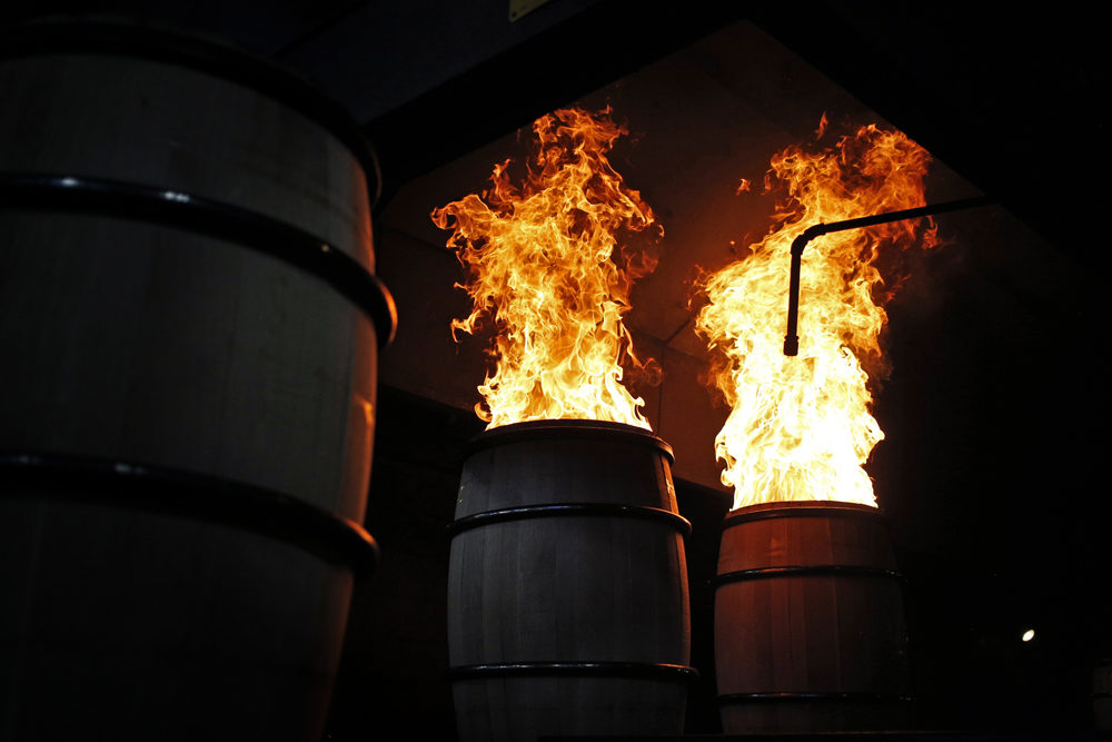 Flames rise from white oak bourbon barrels as they are charred at the Brown-Forman Cooperage in Louisville, Ky. (Luke Sharrett for Here & Now)