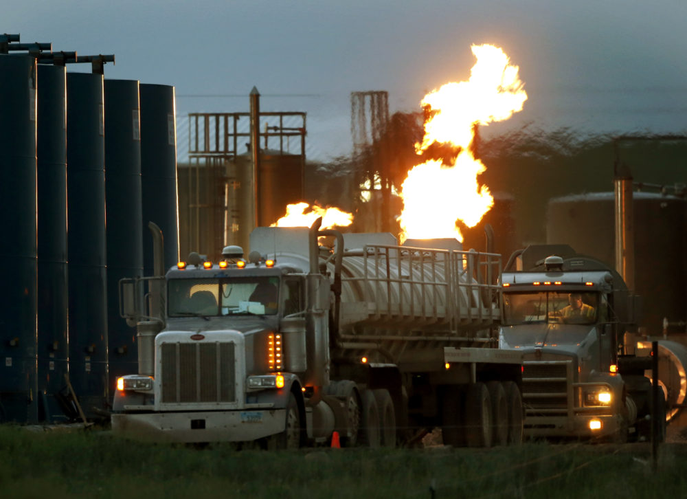 In this June 9, 2014 file photo, drivers and their tanker trucks, capable of hauling water and hydraulic fracturing liquid, line up near a natural gas burn off flame and storage tanks in Williston, N.D. (Charles Rex Arbogast/AP)