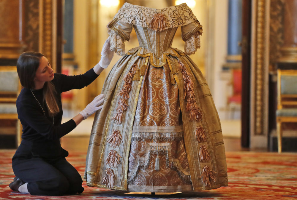 A member of the Palace staff arranges Queen Victoria's Stuart Ball costume which is part of an exhibition to mark the 200th anniversary of the birth of Queen Victoria (1819–1901) this year at Buckingham Palace in London. (Frank Augstein/AP)