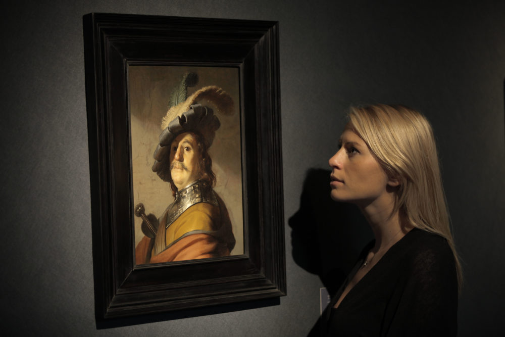 "An auction house worker poses in front of a Rembrandt masterpiece entitled ""A Bust of a Man in a Gorget and Cap"" that was sold at auction for 8.4 million pounds in London 2012. (Lefteris Pitarakis/AP)"