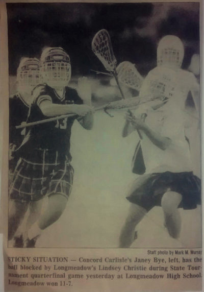 A newspaper clipping showing Longmeadow girls' lacrosse players donning youth ice hockey helmets. (Courtesy Kathy Tomassetti)