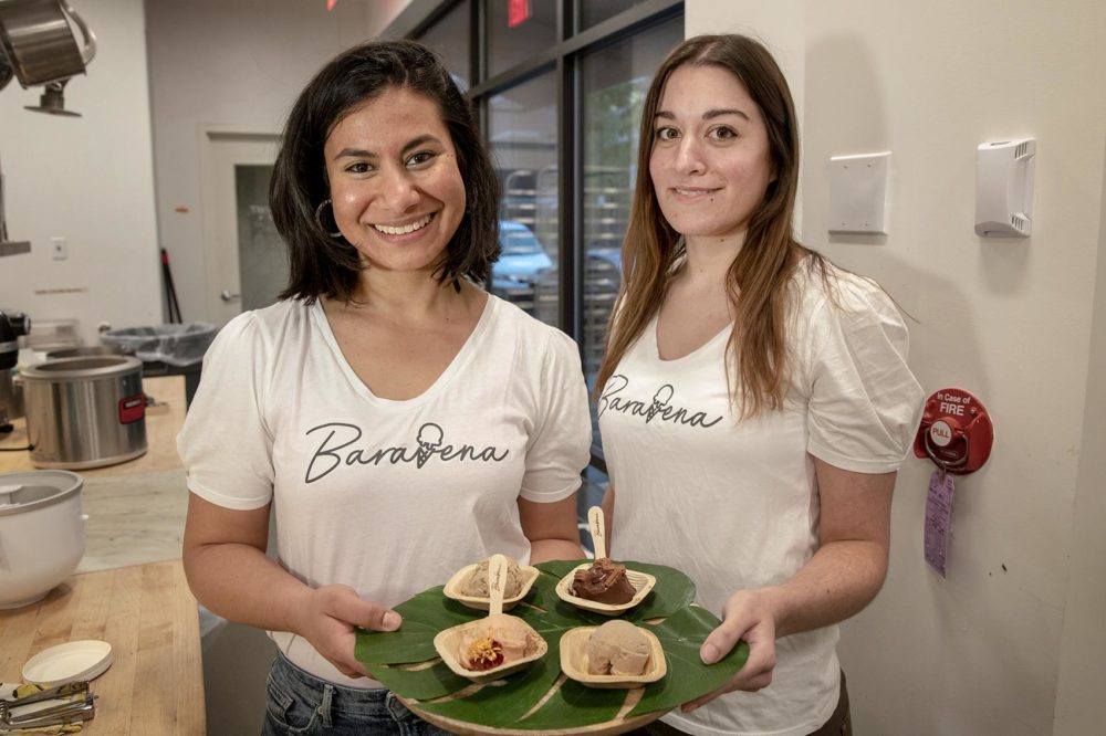 Baravena's Nayla Bezares stands with her partner Sylvia Berciano Benitez. The two doctoral students at Tufts show the various helado flavors they've concocted from oats. (Robin Lubbock/WBUR)