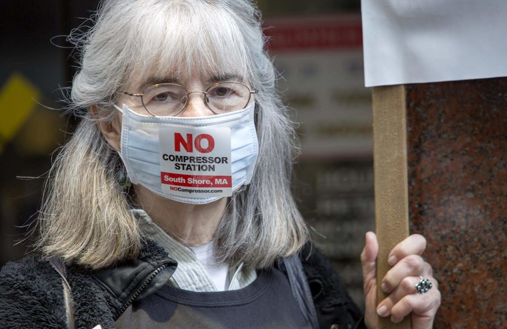 "Barbara Baatz wears a face mask and ""No Compressor Station"" sticker at a May protest against the development of the Weymouth compressor station. (Robin Lubbock/WBUR)"