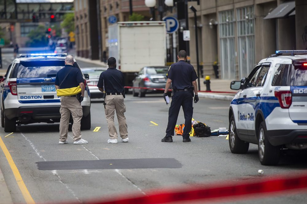 Boston police examine evidence on the ground in front of the Colonnade Hotel on Huntington Avenue following a shooting that claimed one life. (Jesse Costa/WBUR)
