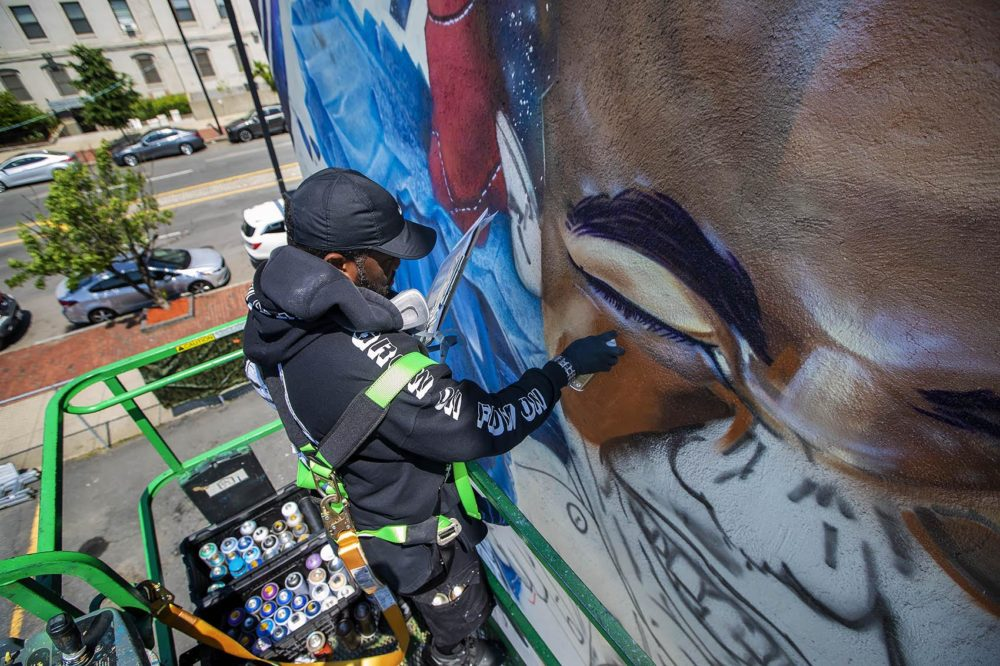 "Artist Rob ""Problak"" Gibbs paints ""Breathe Life 3"" on the side of a three story building. (Jesse Costa/WBUR)"