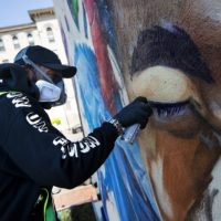 """Artist Rob """"Problak"""" Gibbs spray paints in eyebrows on his latest mural, """"Breathe Life,"""" on the side of 808 Tremont St., a three story building in Roxbury. (Jesse Costa/WBUR)"""