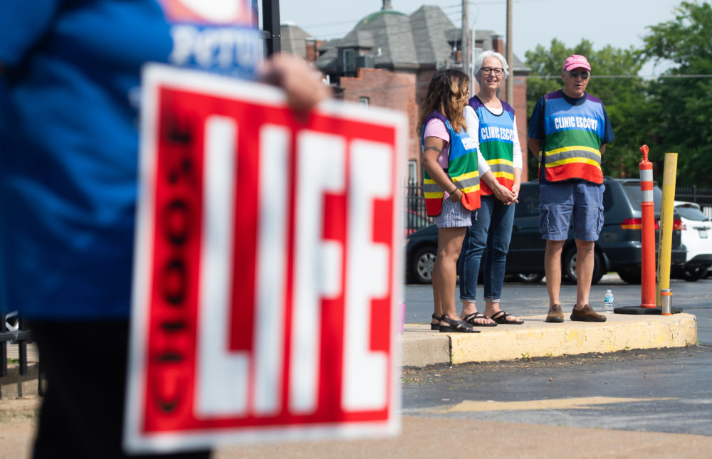 Clinic escorts stand in the parking lot as anti-abortion demonstrators hold a protest outside the Planned Parenthood Reproductive Health Services Center in St. Louis on May 31, 2019, the last location in the state performing abortions. (Saul Loeb/AFP/Getty Images)