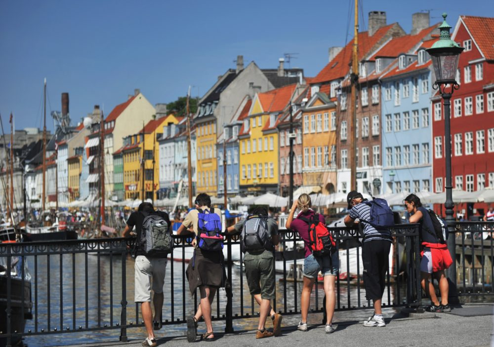 Tourists stand on a bridge and look at colorful houses in the Nyhavn district of Copenhagen, Denmark. (Johannes Eisele/AFP/Getty Images)