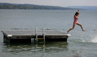 A young swimmer jumps into Skaneateles Lake in Skaneateles, N.Y. The small lakeside town in upstate New York's Finger Lakes is just one of many destinations you could consider visiting this summer. (Kevin Rivoli/AP)
