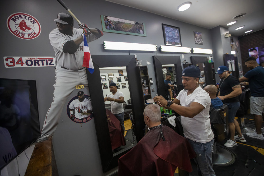 With the walls adorned with images of Big Papi, Gino Almonte gives a haircut to a patron at MLB Barbers on Tremont Street, where David Ortiz gets his hair cut regularly. (Jesse Costa/WBUR)