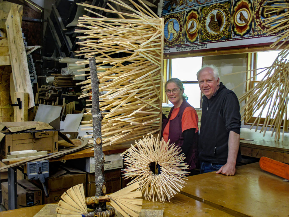 """Laura and Rick Brown at Handshouse Studio, next to a small scale model of """"Singing Tree,"""" one of the planned sculptures for the Chesterwood exhibit. In the lower left is a model of """"Mother Tree."""" (Penny Schwartz for WBUR)"""