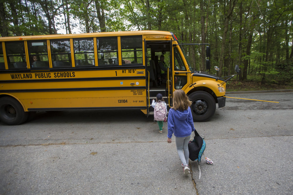 Anya, foreground, and a friend board their Wayland school bus. The town's school start times are set to shift. (Jesse Costa/WBUR)