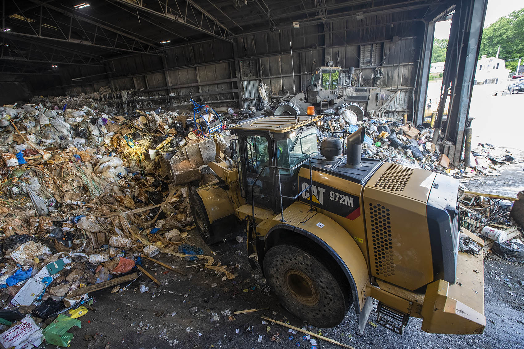 At E.L. Harvey & Sons in Westborough, two land movers push about 1,000 tons of trash into the rear of a warehouse to be baled, packed and shipped out across the country. (Jesse Costa/WBUR)