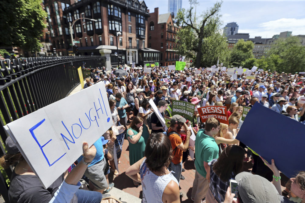 People rally outside the State House in Boston on June 20, 2018, to protest how immigrants are being treated both on the border with Mexico and in Massachusetts. (Elise Amendola/AP)