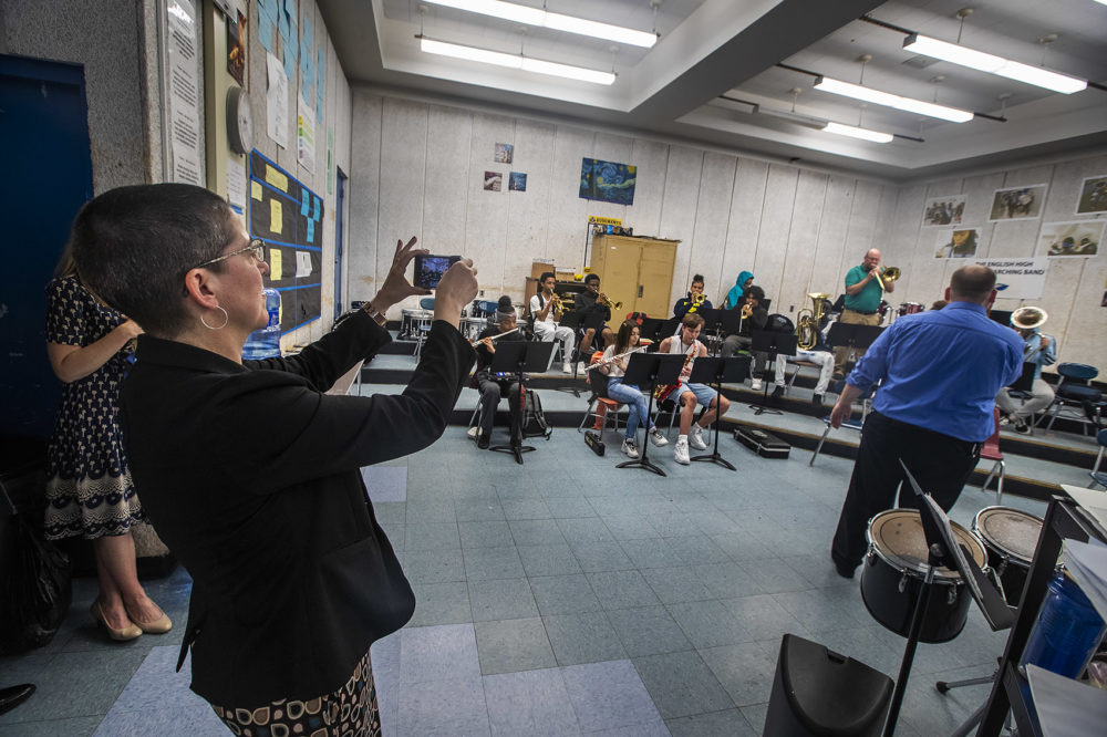 Laura Perille snaps a photo during a rehearsal for English High's marching band, the only marching band at a Boston public school. (Jesse Costa/WBUR)