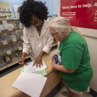 CVS pharmacist Lucy Charlene Wafo reviews Joanne Rhoton's insurance coverage for the prescription order she just picked up. (Jesse Costa/WBUR)