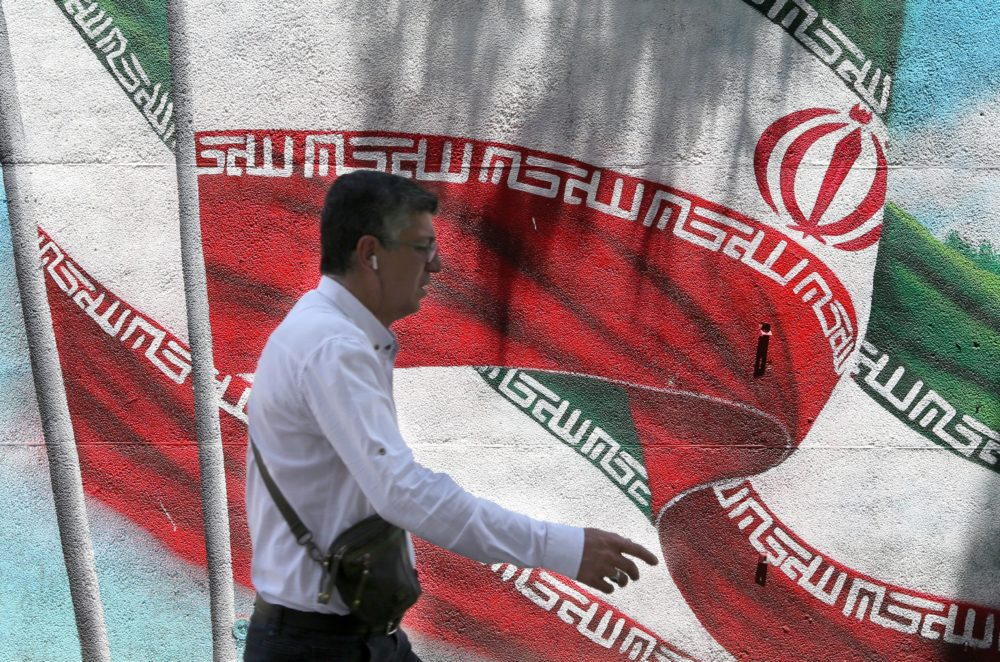 An Iranian man walks past a mural painted with the Iranian flag in Tehran. (Atta Kenare/AFP/Getty Images)