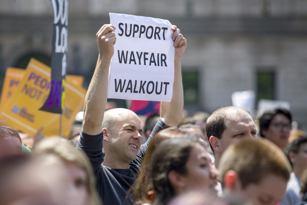 A man in Copley Square holds a sign in support of the Wayfair walkout. (Robin Lubbock/WBUR)