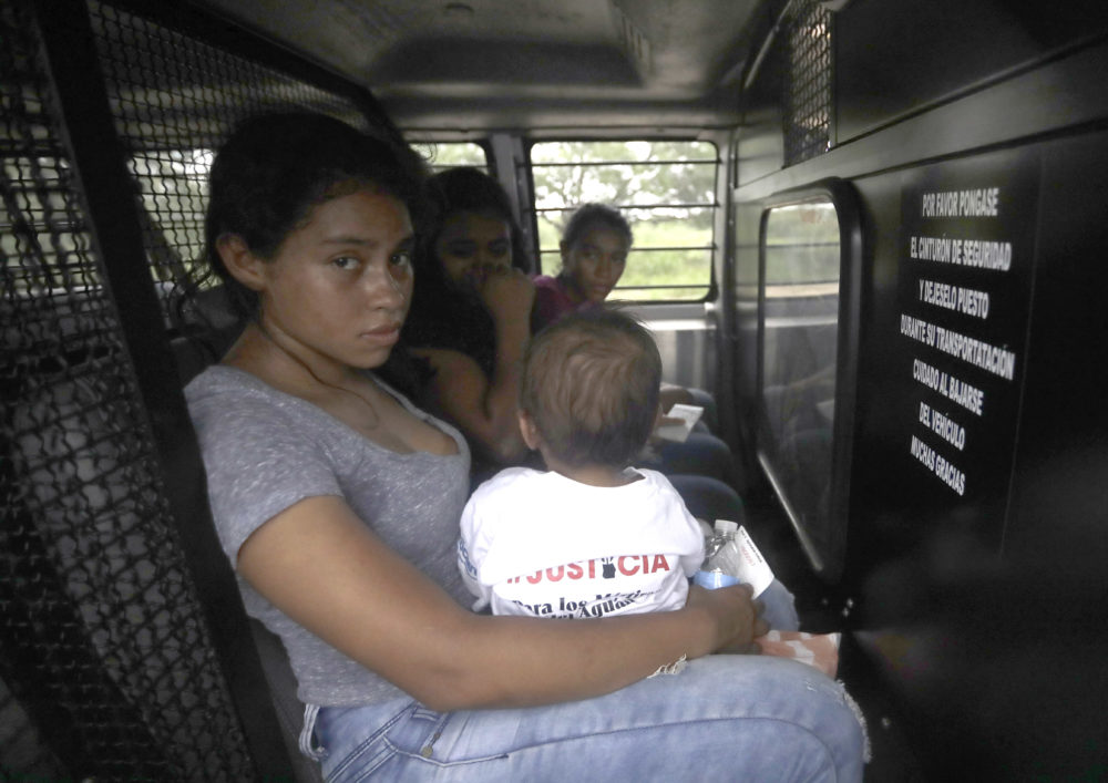 A Honduran woman holds her one-year-old in the back of a transport van after surrendering to U.S. Border Patrol agents Monday, June 25, 2018, near McAllen, Texas. (David J. Phillip/AP)