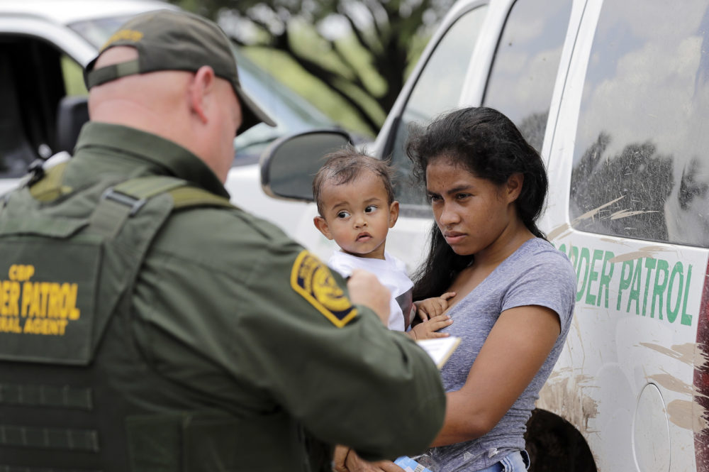 In this June 25, 2018 file photo, a woman from Honduras and her 1-year-old child surrender to U.S. Border Patrol agents after crossing the border, near McAllen, Texas. (David J. Phillip/AP)