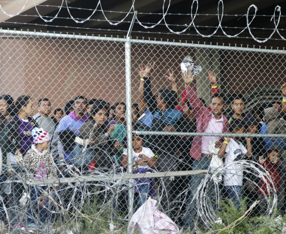 In this March 27, 2019, file photo, Central American migrants wait for food in a pen erected by U.S. Customs and Border Protection in El Paso, Texas. (Cedar Attanasio/AP)