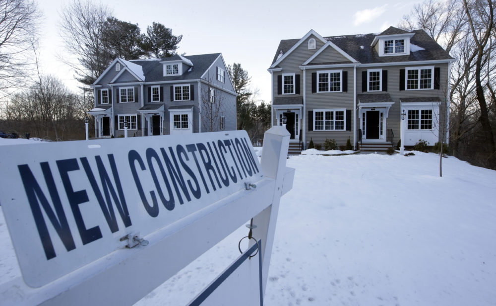 Newly constructed homes sit near a sign in Natick. (Steven Senne/AP)