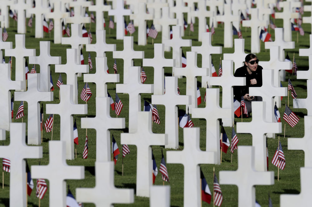 A young woman visits headstones of World War II soldiers prior to a ceremony to mark the 75th anniversary of D-Day at the Normandy American Cemetery in Colleville-sur-Mer, Normandy, France, Thursday, June 6, 2019. (David Vincent/AP)