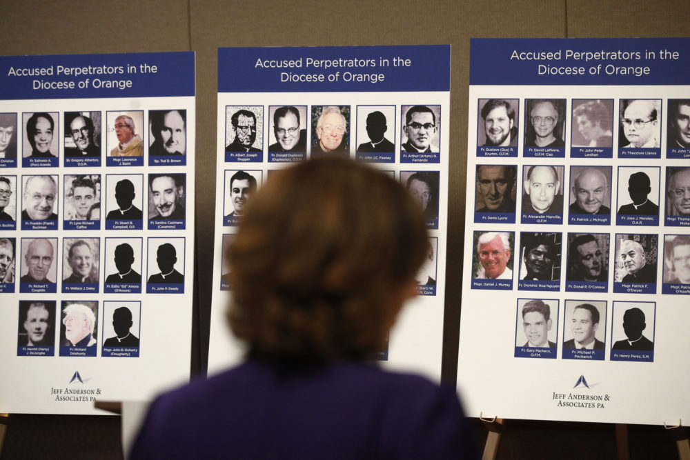 An advocate and survivor of sexual abuse looks at the photos of Catholic priests accused of sexual misconduct by victims during a news conference in Orange, Calif in 2018. (Jae C. Hong/AP)