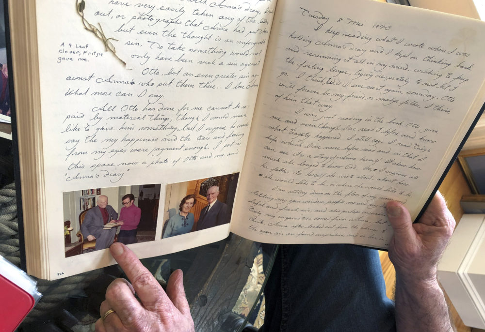 Ryan Cooper is pointing to a photo of him with Otto Frank while holding Anne's original diary. (Philip Marcelo/AP)