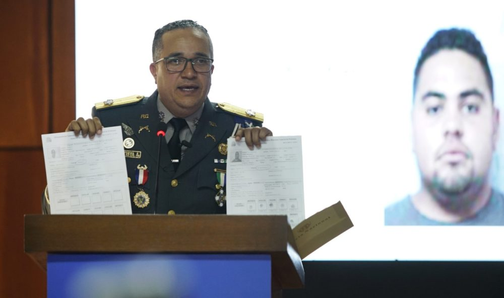 Earlier in June, the director of the National Police, Maj. Gen. Ney Aldrin Bautista Almonte, gives details on the attack on David Ortiz, in front of an image of Victor Hugo Gomez. According to Rodríguez, Ortiz was shot by a gunman who mistook him for the real target, Sixto David Fernández, and the attempted murder was ordered from the United States by Hugo Gomez, Fernández's cousin. (Roberto Guzman/AP)