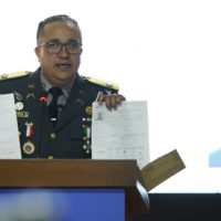 The director of the National Police, Maj. Gen. Ney Aldrin Bautista Almonte, gives new details Thursday on the attack on David Ortiz, in front of an image of Victor Hugo Gomez. According to Rodríguez, Ortiz was shot by a gunman who mistook him for the real target, Sixto David Fernández, and the attempted murder was ordered from the United States by Hugo Gomez, Fernández's cousin. (Roberto Guzman/AP)