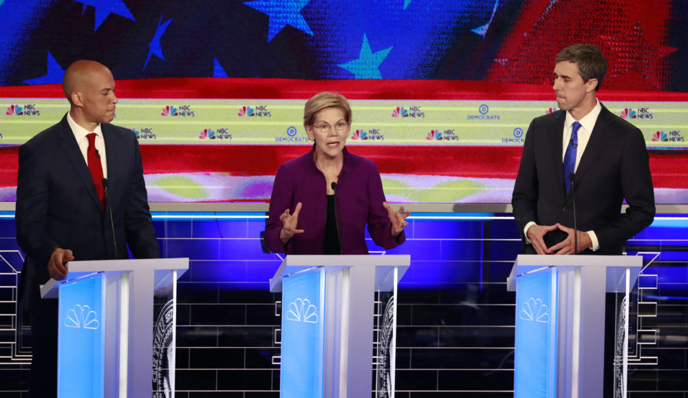 Democratic presidential candidate Sen. Elizabeth Warren answers a question as Sen. Cory Booker, D-N.J., and former Texas Rep. Beto O'Rourke, listen at the first presidential debate in Miami, on Wednesday evening. (Wilfredo Lee/AP)