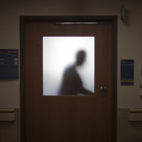 In this Jan. 24, 2014 photo, a doctor is silhouetted against a glass window while leaving an exam room after visiting a patient at Grady Memorial Hospital, in Atlanta. (David Goldman/AP)