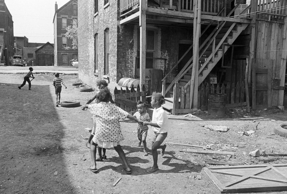 African-American children use a backyard in the slums of Chicago, Ill., as a playground, July 24, 1967. Most of the 324,000 people who live in this section of the West Side were black and poor. (Charles Knoblock/AP)