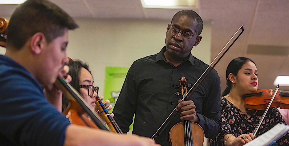 David France instructs members of his Roxbury Youth Orchestra. (Jesse Costa/WBUR)